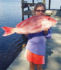 Katlyn holding up a red snapper she caught.