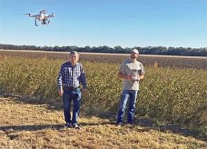 ARS agricultural engineer Yanbo Huang (left) and technician Ryan Poe use a drone to identify glyphosate-resistant weeds in a Mississippi soybean field. Photo by Daniel Fisher.
